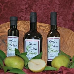 three bottles of olive oil and cutting board
